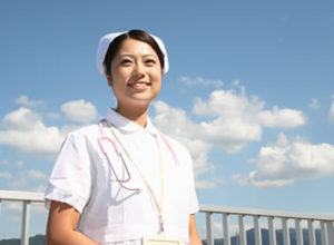 スタッフ採用情報/青空に雲の背景屋上にて女性看護師さんのすがすがしい笑顔